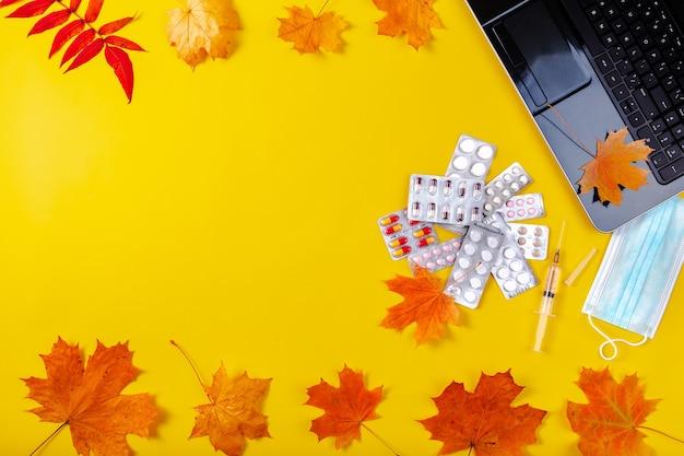 Планшетный компьютер с маской и бутылкой дезинфицирующего средства с осенними листьями.