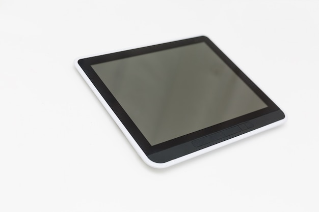 Tablet computer with blank screen mockup lies on the surface, isolated on white background.