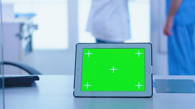 의사 캐비닛에 복사 공간이 있는 태블릿 컴퓨터. 엑스레이 이미지를 들고 있는 어시스턴트. 병원의 유리 벽을 통해 크로마 키가 있는 태블릿 컴퓨터의 전망.