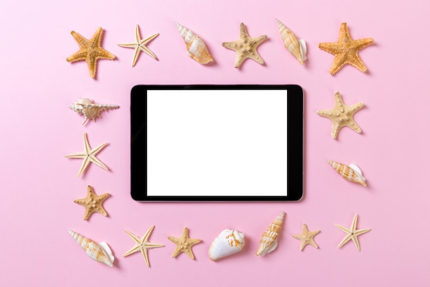 Tablet computer with seashells on pink background. technology vacation holidays concept.