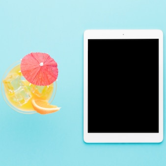 Tablet and cool cocktail on light background