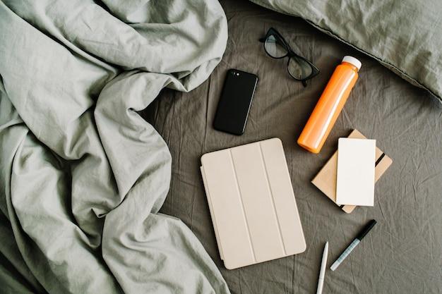 Планшет, дневник, мобильный, свежий сок, стаканы в постели с серой простыней и подушками