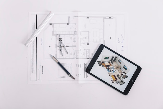 Tablet and drafting tools on blueprint