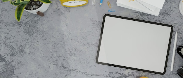 Tablet empty screen stylus pen clock plants stuff and copy space on loft table in grey colour