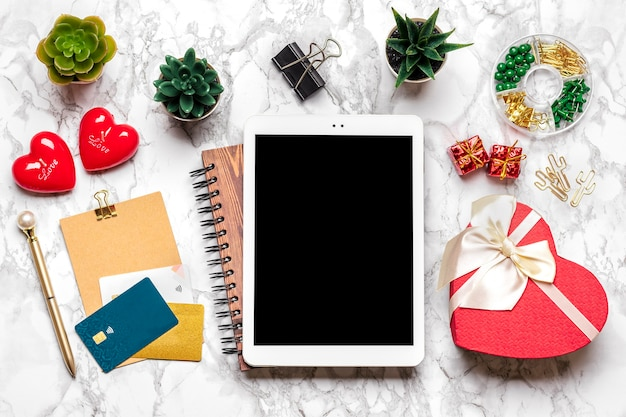 ギフトを選択するためのタブレット、購入、コーヒー、デビットカード、ボックス、バッグ、大理石のテーブルに2つのハート
