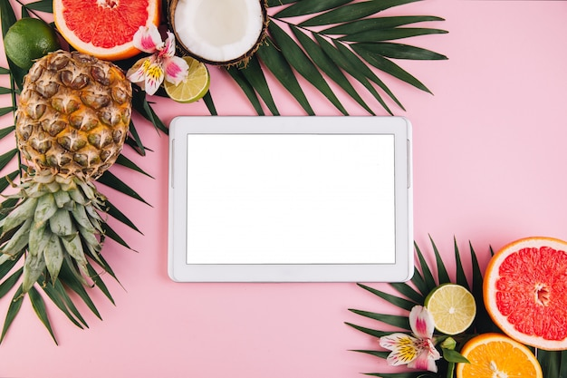 Tablet frame around summer fruit composition on pink table. flat lay, top view, copy space