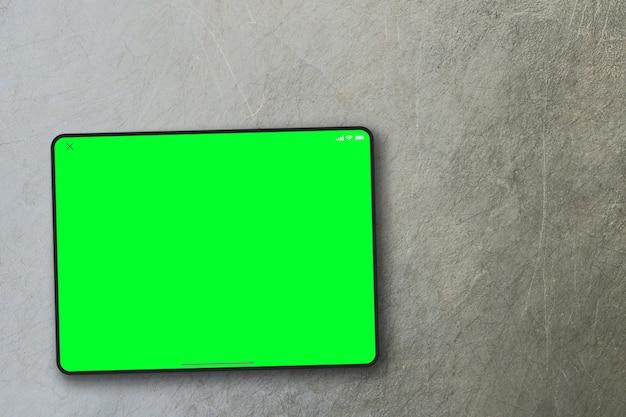 시멘트 배경에 태블릿 녹색 화면입니다. 평면도. 크로마 키.