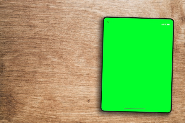나무 배경에 태블릿 녹색 화면입니다. 평면도. 크로마 키.