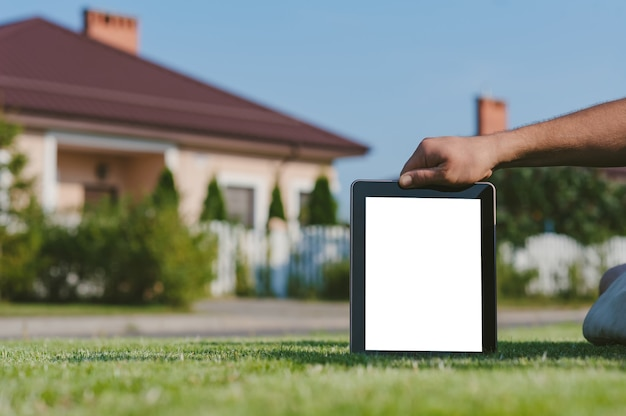 Tablet in hand, on the lawn against the backdrop of the house.