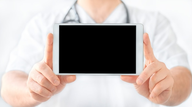 白い背景の上の医師の手にタブレット
