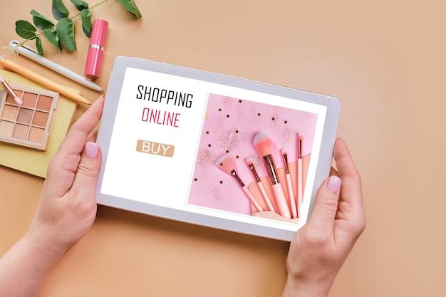 化粧品店の開いたウェブページで女性の手にタブレット