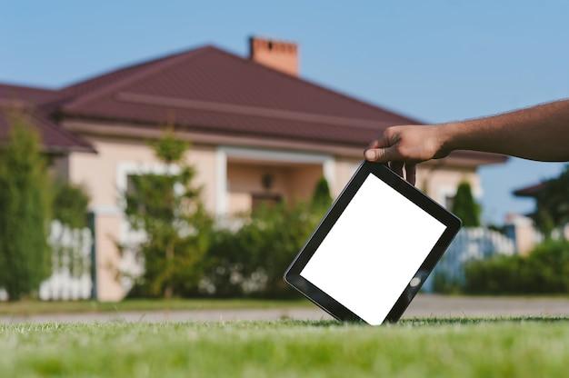家を背景に芝生の上で、手にタブレット。