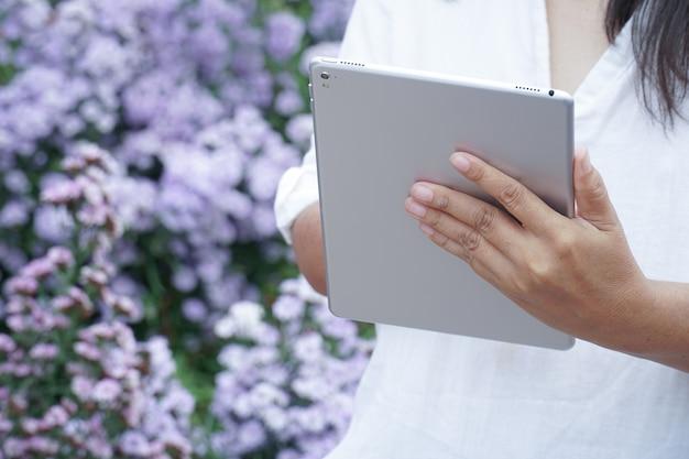 Таблетка в руках женщины, ученый, наблюдающий за фиолетовыми цветами растений.