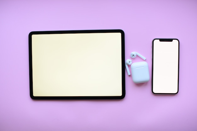 Tablet and l and air pods on pink background