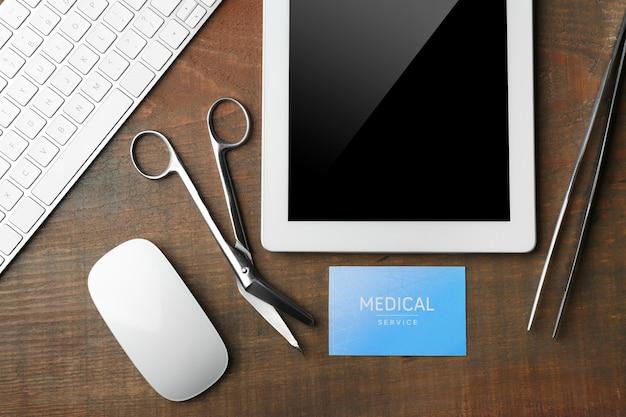 木製のタブレット、医療ツール、名刺。医療サービスの概念