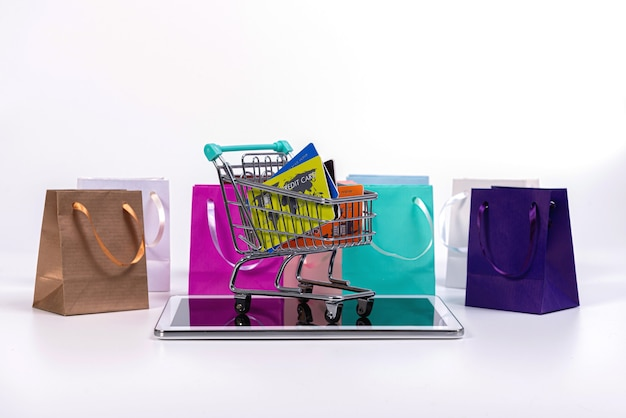 Tablet, mini shopping cart with credit cards and colourful paper bags isolated on white, e-commerce