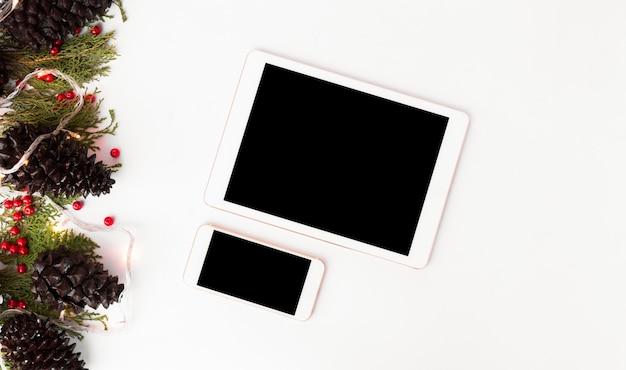 タブレットモバイルディスプレイクリスマス、モミの枝松コーンフラットレイ背景