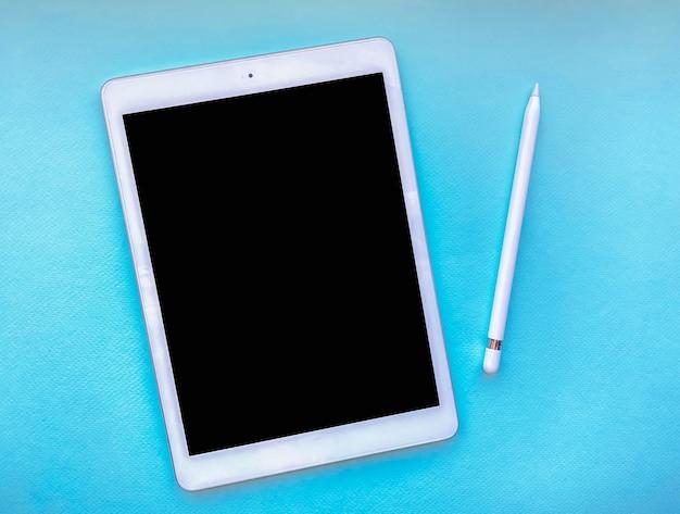Планшетный макет на столе со стилусом, изолированным на синем фоне. бизнес-концепция.