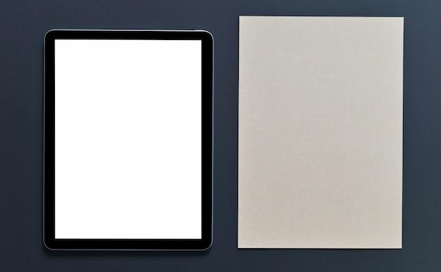 Пустой экран планшета макета и коричневый блокнот на черном