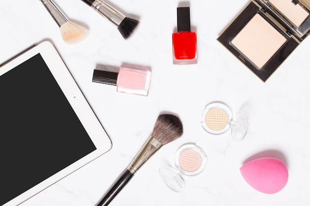 Tablet near cosmetics on white