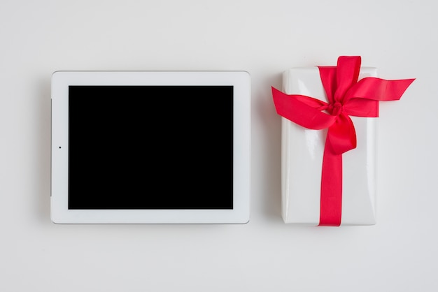 Tablet near gift box with red ribbon