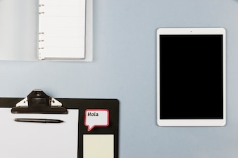 Tablet near notebook, clipboard with paper and frame with Hola inscription
