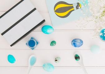 Планшет рядом с бумагой с рисунком и пасхальными яйцами между цветочной веточкой и банками с жидким красителем