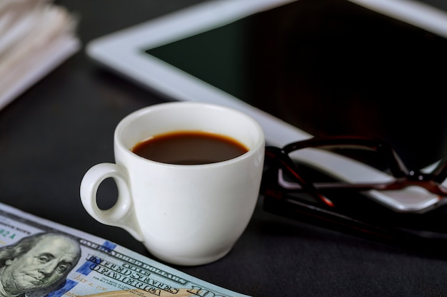 Tablet notepad, glasses and espresso coffee cup in the office cash american of us 100 dollars