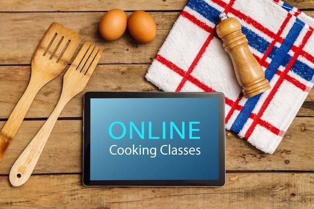 素朴なテーブルの上にタブレット、テキスト付きの台所用品、青の料理教室