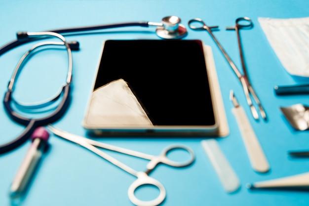 파란색 표면에 태블릿 pc와 의사 도구입니다. 의료 개념