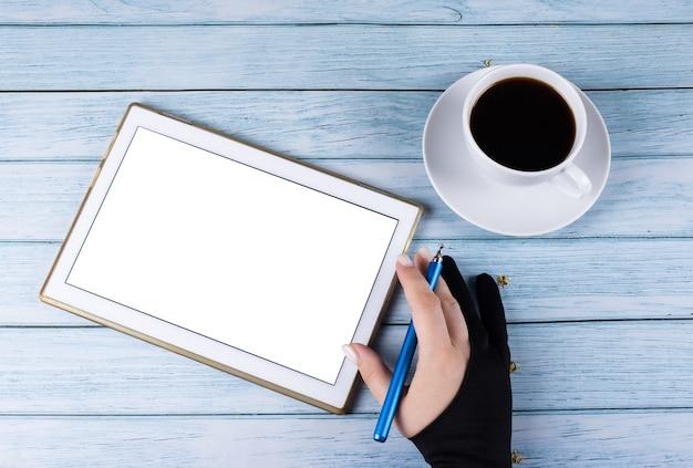 스타일러스 작업 프로세스가 있는 나무 배경 손에 있는 커피 한 잔 근처의 태블릿 pc