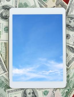 画面上のお金のドルの背景の雲の空の中心に配置されたタブレットpc