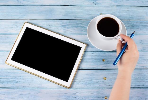 스타일러스 작업 프로세스가 있는 나무 배경 손에 검은색 화면이 있는 태블릿 pc 온라인 교육