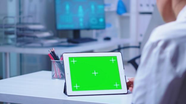 흰색 코트를 입고 의사가 사용하는 병원 캐비닛에 녹색 화면이 있는 태블릿 pc. 파란색 제복을 입은 간호사가 진료소에 입장합니다. 교체 가능한 화면이 있는 태블릿 컴퓨터에서 작업하는 건강 클리닉의 의사
