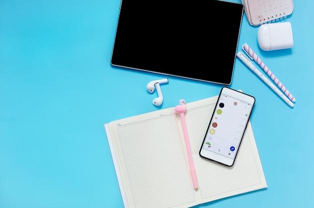 Планшетный телефон наушники ноутбук школьные принадлежности на синем фоне