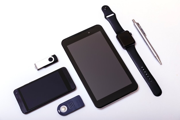 Tablet, phone, pendrive, pens, watch on white
