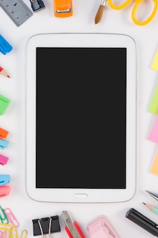 Tablet phone and school or office tools  on white background