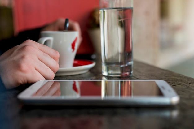 Tablet placed on table near cup with beverage
