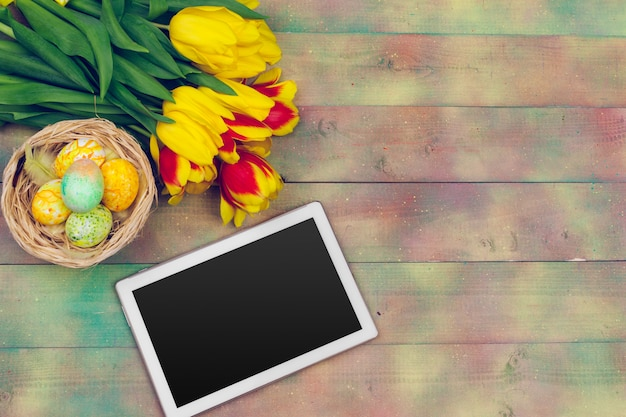 Tablet screen for message and colorful tulips and easter eggs on wooden background
