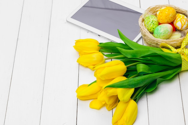Tablet screen  message and colorful tulips and easter eggs on wooden