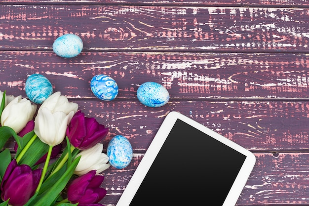 Tablet screen for message and colorful tulips and easter eggs on wooden