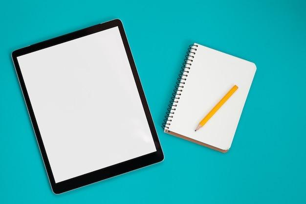 파란색 배경, 위쪽 보기에 격리된 태블릿 화면 모형 및 메모장