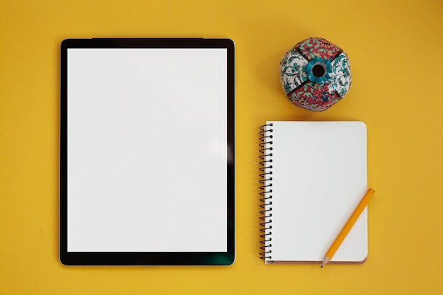 노란색 배경, 위쪽 보기에 격리된 태블릿 화면 모형 및 메모장