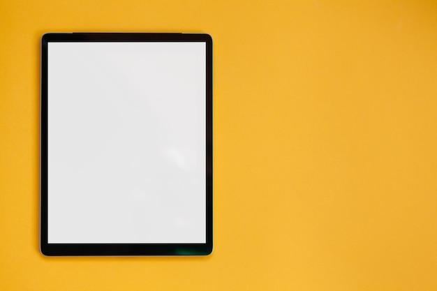 노란색 배경, 상위 뷰에 격리된 태블릿 화면 모형