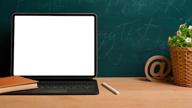 緑の黒板の背景に装飾が施された木製のテーブルの上に魔法のキーボードスタンドとタブレット画面のモックアップ