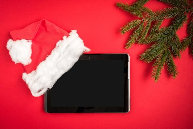 赤のクリスマス帽子とモミの枝とタブレット画面。
