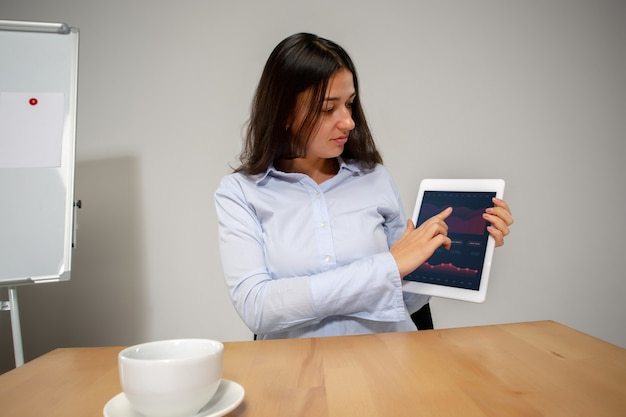 Tablet screen young woman working in videoconference with colleagues coworkers at office