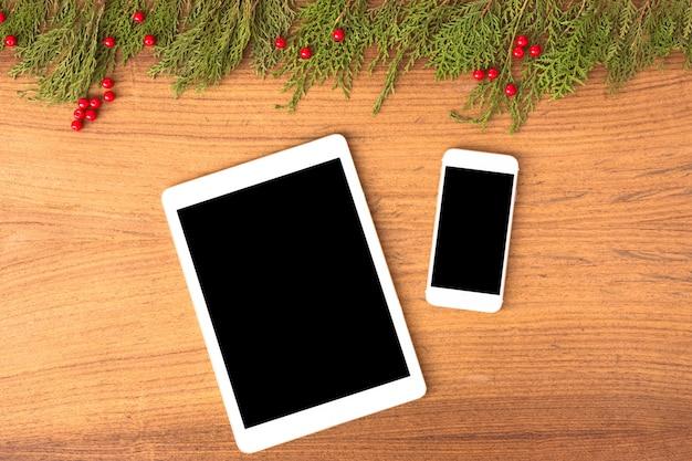 テーブル上のタブレットスマートフォンのモバイルディスプレイ。クリスマスの時期。