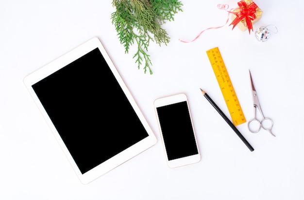 キリストのモックアップのための孤立した白い画面のテーブルにタブレットスマートフォンモバイルディスプレイ