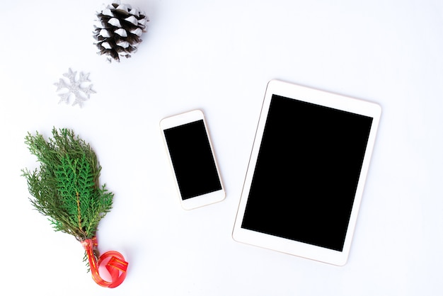クリスマスの時間にモックアップのための孤立した白い画面のテーブルにスマートフォンのモバイルタブレットを表示